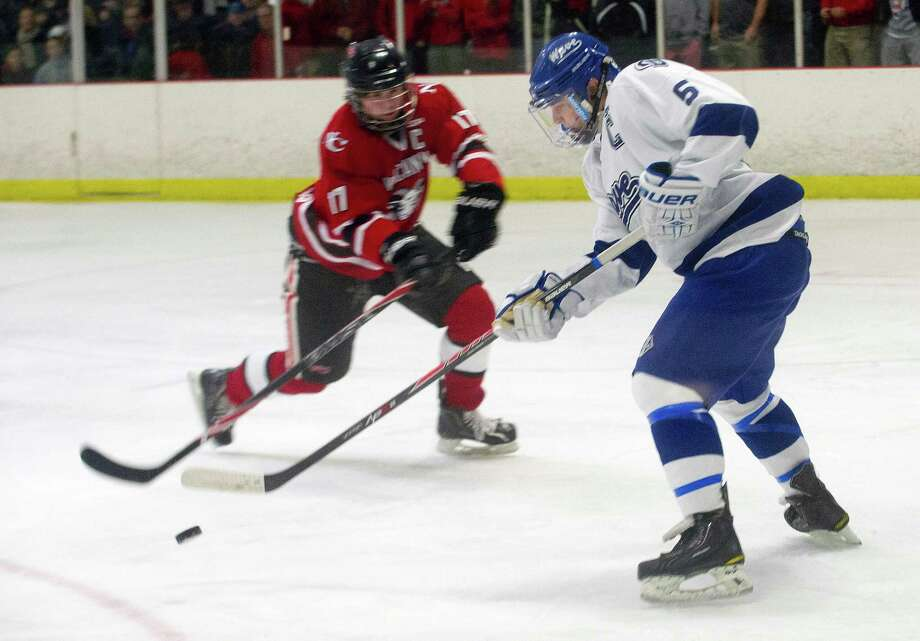 Darien's Owen Koorbusch, right, and New Canaan's Steve Mettler, left, compete for control of the puck during Saturday's boys hockey game at the Darien Ice Rink in Darien, Conn., on December 28, 2013. Photo: Lindsay Perry / Stamford Advocate