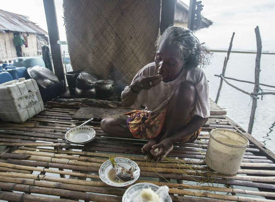 Honna, a Bajau villager, has a fish meal. Carbon dioxide emissions may someday curtail her food supply. Photo: Steve Ringman, MBR / Seattle Times