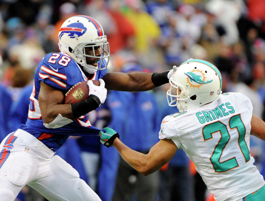 Buffalo Bills running back C.J. Spiller (28) straight-arms Miami Dolphins cornerback Brent Grimes (21) during the second half of an NFL football game on Sunday, Dec. 22, 2013, in Orchard Park, N.Y. (AP Photo/Gary Wiepert) ORG XMIT: NYMG114 Photo: Gary Wiepert / FR170498 AP