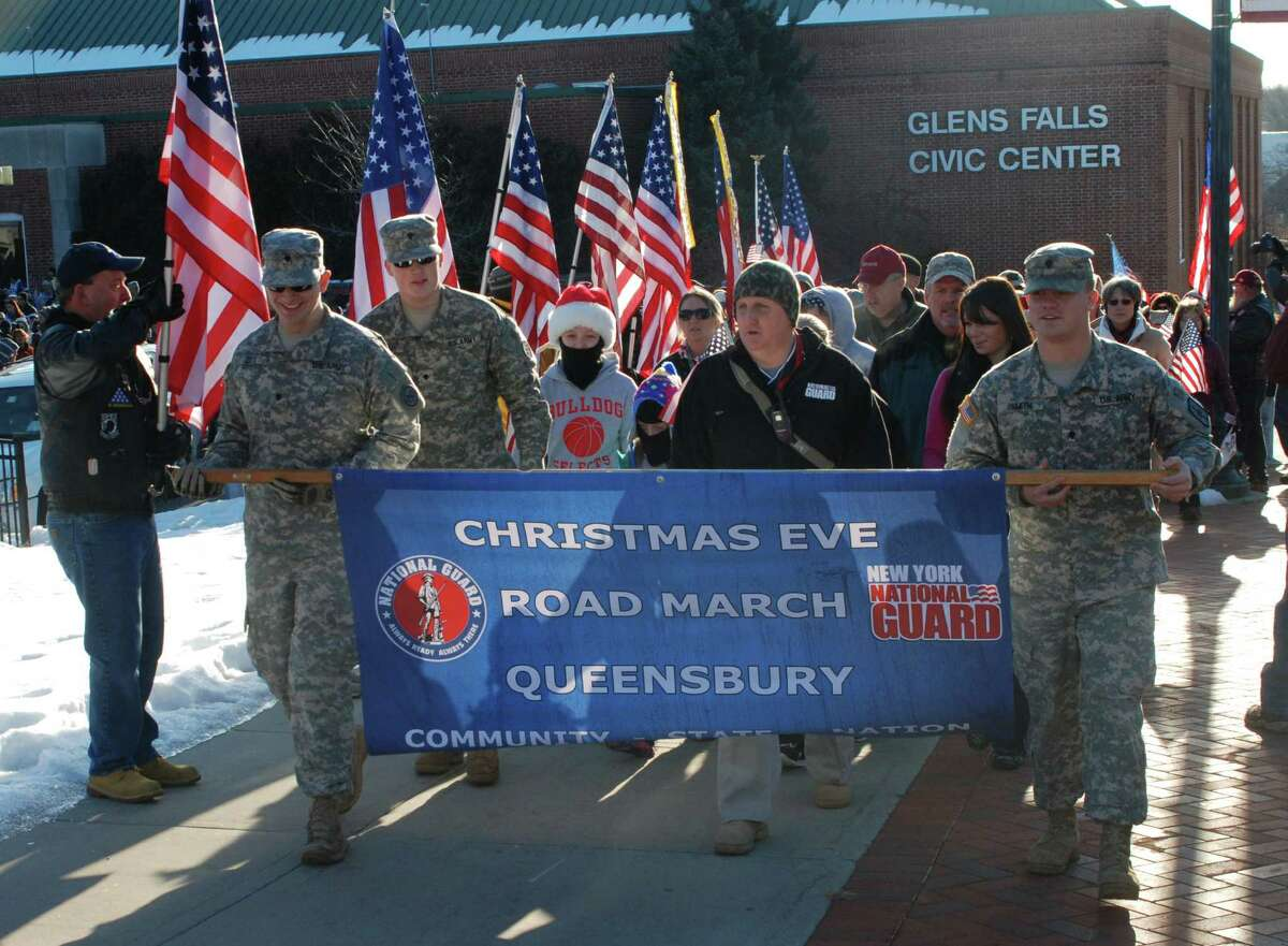 Col. Richard Goldenberg / Joint Forces Headquarters New York Army National Guard Spcs. James Zito, from left, of South Glens Falls, Nicolas Cassey of Gansevoort and Russell Smith of Queensbury assist event organizer and retired Army National Guard Sgt. 1st Class Art Coon as they lead the participants of the 10th Christmas Eve Road March.