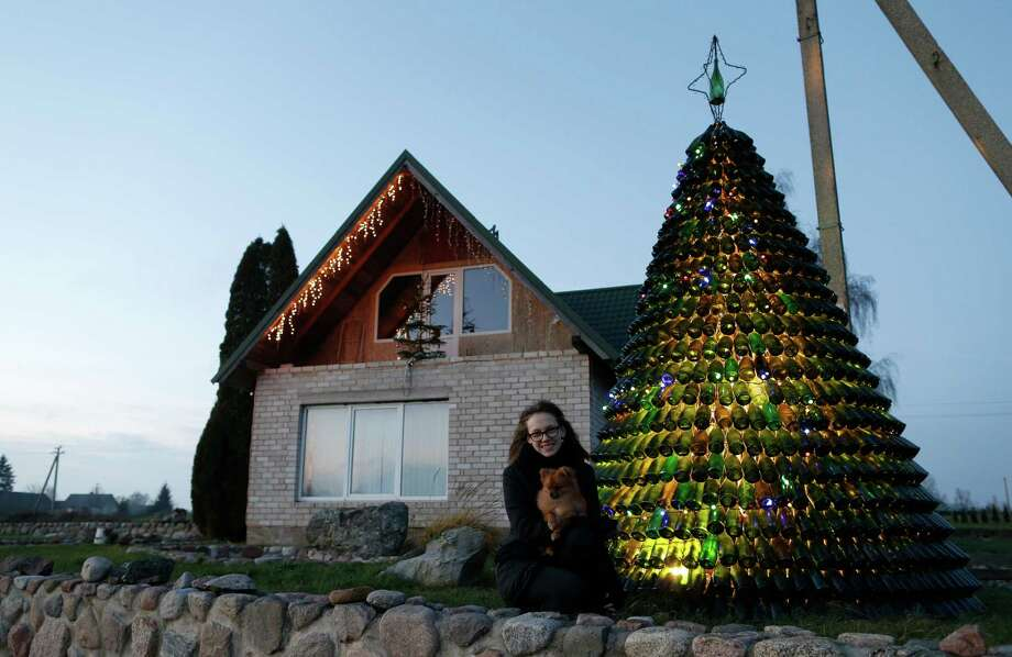 Goda Valukonyte shows off the bottle Christmas tree in Agariniu. Lithuanian policeman Dalius Valukonis says he spent three years creating the tree.  Photo: Mindaugas Kulbis, STR / AP