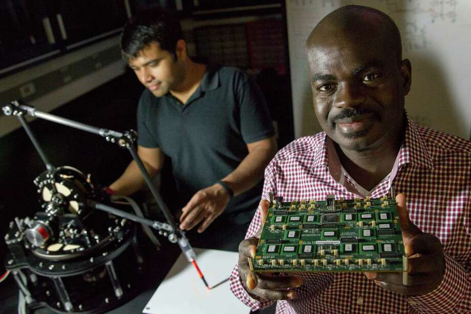 Kwabena Boahen, right, and student Samir Menon demonstrate the use of a biologically inspired processor attached to a robotic arm in a Stanford University laboratory in Palo Alto, Calif. Photo: ERIN LUBIN, STR / NYTNS