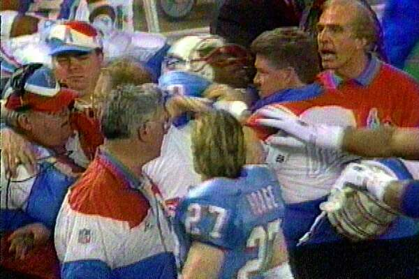 Oilers players and coaches intervene after defensive coordinator Buddy Ryan, left with headset, threw a punch at offensive coordinator Kevin Gilbride, right with back toward camera, during a sideline confrontation in the '93 regular-season finale.