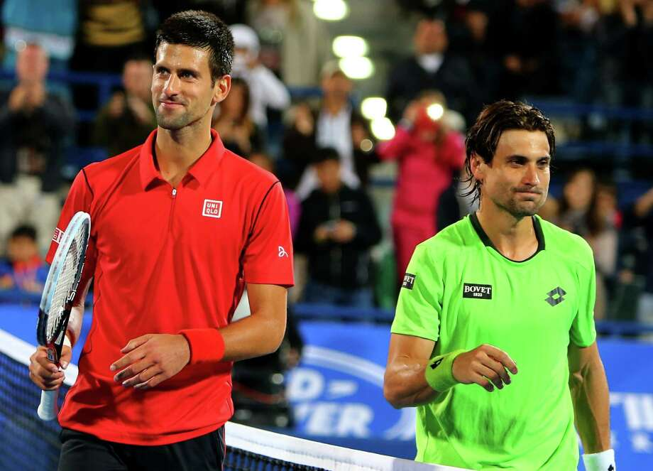 Novak Djokovic, left, dispatched David Ferrer in straight sets to win the World Tennis Championship title and  finish the year with a 24-match winning streak on the ATP tour. Photo: MARWAN NAAMANI, Staff / AFP