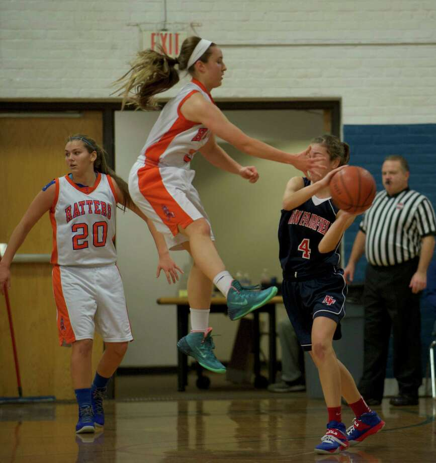 Danbury's Rachel Gartner (5) jumps to block a pass by New Fairfield's Bridget Zima (4) during the News-Times Greater Danbury Tip Off Classic girls basketball tournament championship game, between Danbury High School and New Fairfield High School, held at the Danbury War Memorial, Danbury, Conn, on Saturday, December 28, 2013. Photo: H John Voorhees III / The News-Times Freelance