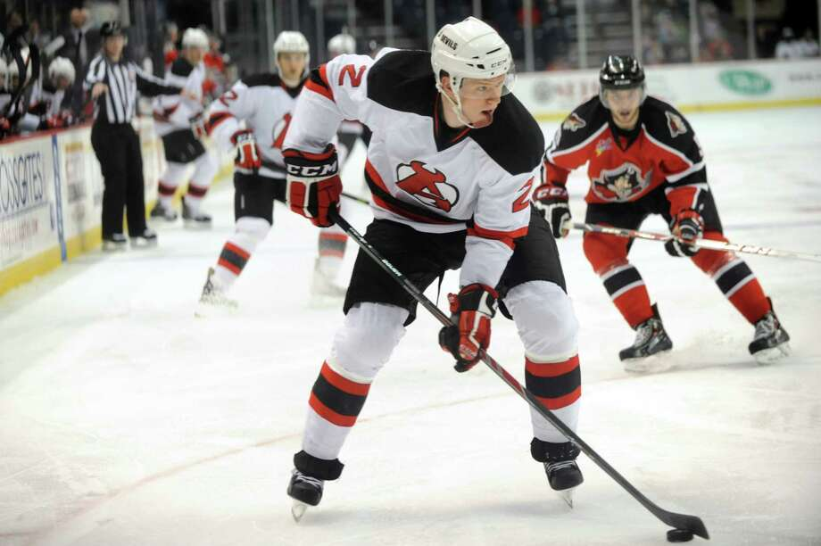 Devils' Seth Helgeson, center, controls the puck during their hockey game against the Portland Pirates on Saturday, Dec. 28, 2013, at Times Union Center in Albany, N.Y. (Cindy Schultz / Times Union) Photo: Cindy Schultz / 00025187A