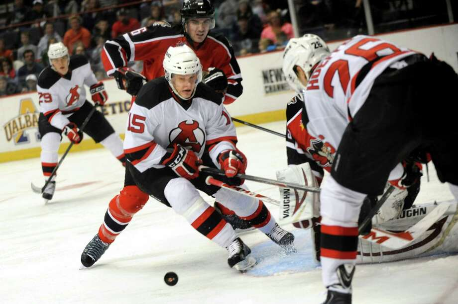 Devils' Harri Pesonen, center, chases a loose puck in front of the net during their hockey game against the Portland Pirates on Saturday, Dec. 28, 2013, at Times Union Center in Albany, N.Y. Photo: Cindy Schultz / 00025187A