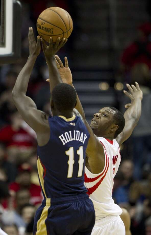 Rockets power forward Terrence Jones (6) defends a shot by Pelicans point guard Jrue Holiday. Photo: Brett Coomer, Houston Chronicle