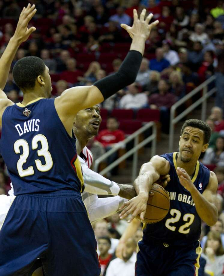 Rockets power forward Dwight Howard (12) is fouled by Pelicans point guard Brian Roberts (22) as he goes to the basket against Roberts and  Pelicans power forward Anthony Davis. Photo: Brett Coomer, Houston Chronicle