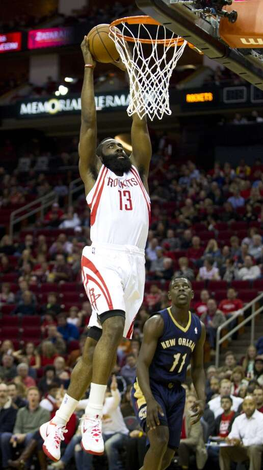 Rockets shooting guard James Harden (13) leaps past Pelicans point guard Jrue Holiday (11) for a dunk. Photo: Brett Coomer, Houston Chronicle