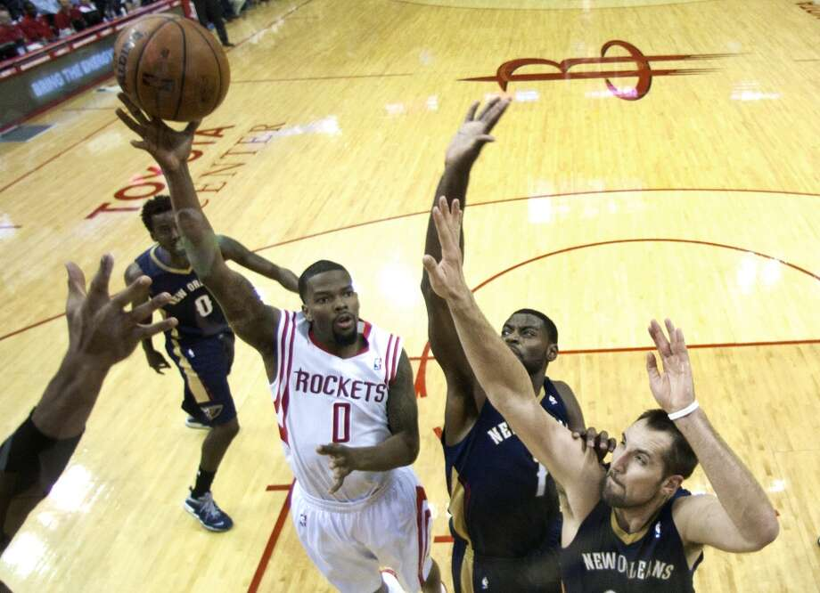 Rockets point guard Aaron Brooks (0) shoots over Pelicans point guard Tyreke Evans (1) and power forward Ryan Anderson (33). Photo: Brett Coomer, Houston Chronicle