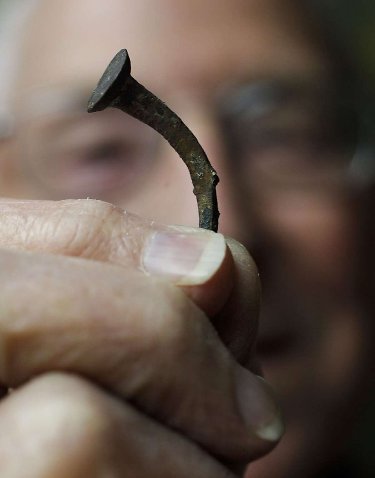 Herb Ford, holds a nail salvaged from the HMS Bounty and now on display at the Pitcairn Islands Study Center on the campus of Pacific Union College on Wednesday Dec. 18, 2013, in Angwiun, Ca. The center is considered to have the world's biggest and best archive on the mutiny on the bounty story of 1789 and was founded by Herb Ford, 84, a former teacher at the college.