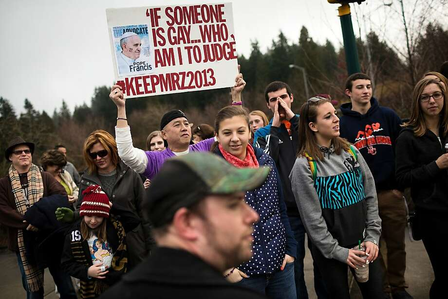 A crowd of nearly 30 students and supporters rally for former Eastside Catholic Vice Principal Mark Zmuda, who resigned his position after officials with the Archdiocese discovered that he was in a same-sex marriage and said he violated his contract, Saturday, Dec. 28, 2013, outside the school in Sammamish, Wash. (AP Photo/seattlepi.com, Jordan Stead) Photo: Jordan Stead, Associated Press