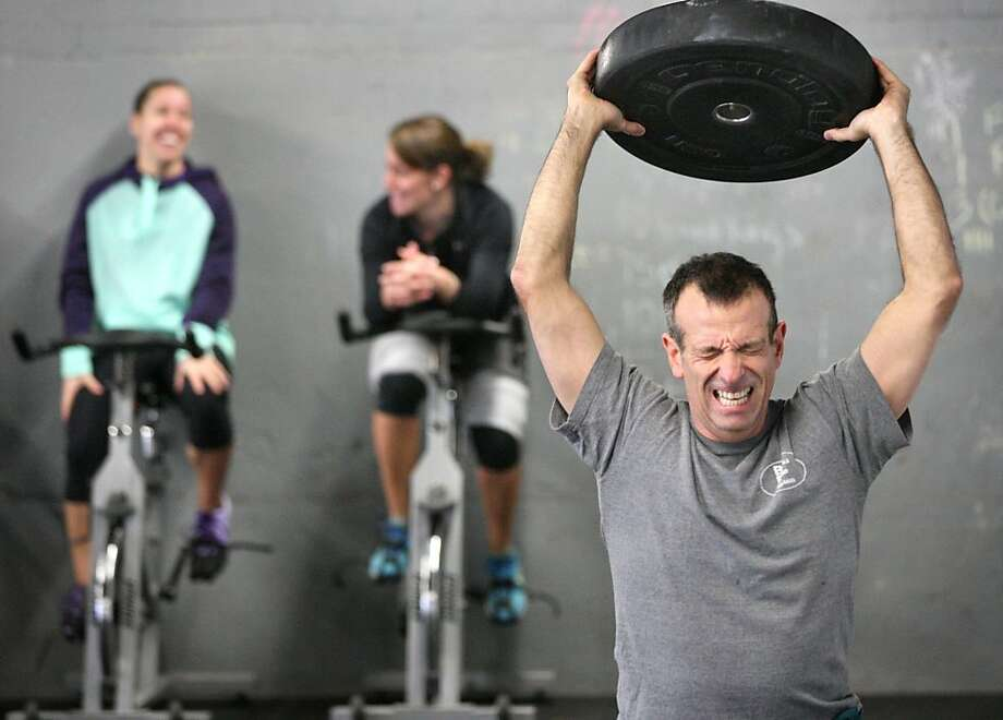 David Feese of Front Royal, Va. grimaces as he lunges holding a weight over his head during a fundraiser  Saturday, Dec. 28, 2013 at Shenandoah Crossfit in Winchester, Va.  for a Stephens City, Va. boy with neurological disorder that expert doctors can't diagnose.  (AP Photo/The Winchester Star, Jeff Taylor) Photo: Jeff Taylor, Associated Press