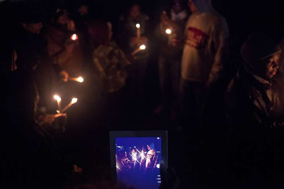 An iPad captures friends and family holding candles Saturday, Dec. 28, 2013 in Flint Township, for Monica Campbell, 42, who was killed Thursday, Dec. 19, after being hit by two vehicles, police say, at River Forest Drive. (AP Photo/The Flint Journal, Zack Wittman) Photo: Zack Wittman, Associated Press