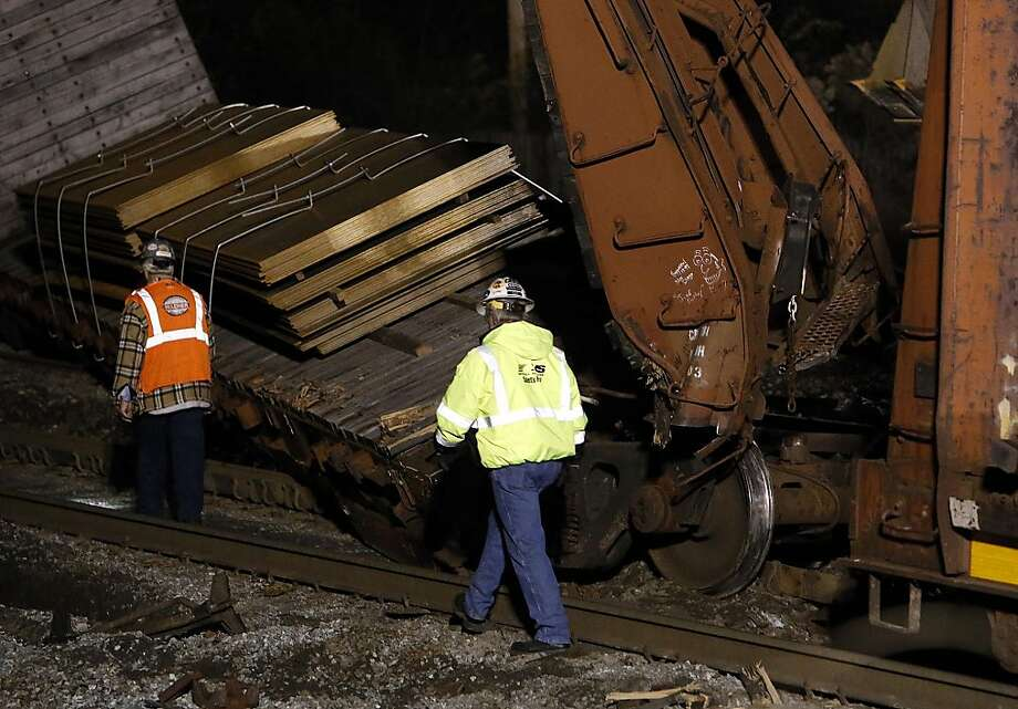 Railroad personnel work to clean up the site of a train derailment early Saturday, Dec. 28, 2013, in Tuscaloosa, Ala. A freight train derailed and lost its load near the intersection of 17th Street and 15th Ave., late Friday night. Workers estimated the site would be cleared by early Saturday morning. (AP Photo/Tuscaloosa News, Dusty Compton) Photo: Dusty Compton, Associated Press
