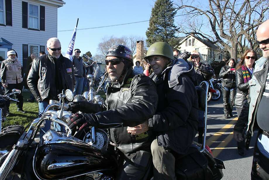 World War II veteran Harold Billow wears a combat helmet while sitting  on the back of a motorcycle on his 91st birthday on Saturday, Dec. 28,  2013 in front of his Mount Joy, Pa., home. Billow, who survived the  Normandy landing and the Malmedy Massacre, was surprised by the visit  from a convoy of veterans of later wars on motorcycles; they rode to Billow's home from nearby Elizabethtown, Pa., escorted by a fire truck. (AP Photo/ The Elizabethtown Advocate, Dan Robrish) Photo: Dan Robrish, Associated Press