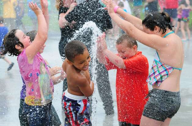 Kennedy Spoon, 9, left, Jayden Johnson, 7, center, Jeremiah Spoon, 6, center right, and Emilee Spoon, right, revel under waters of Green Island's new Spray Park at the Paine Street Park Monday morning, July 1, 2013, in Green Island. The new water park was built with a donation from lottery winners, John and Linda Kutey in honor of their parents Edmund Ostrowski and the late Gertrude Ostrowski and Joseph and Mercedes Kutey, Sr. James Besha, Sr. of Albany Engineering Corp., and Todd Grimm and Grimm Building Materials donated their services to the project. (Will Waldron/Times Union) Photo: Will Waldron, Albany Times Union