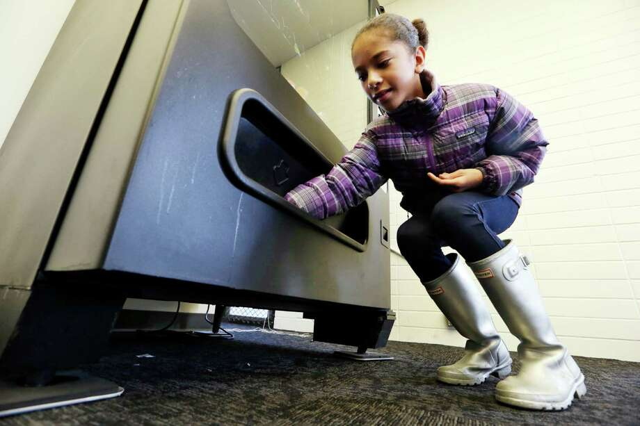 In this Dec. 23, 2013 photo, a 12-year-old girl, who declined to be identified, reaches for the drink she purchased at a vending machine in Seattle. Office workers in search of snacks will be counting calories along with their change under new labeling regulations for vending machines included in President Barack Obama's health care overhaul law. The Food and Drug Administration, which is expected to release final rules early next year, says requiring calorie information to be displayed on roughly 5 million vending machines nationwide will help consumers make healthier choices. Photo: Elaine Thompson, AP / AP