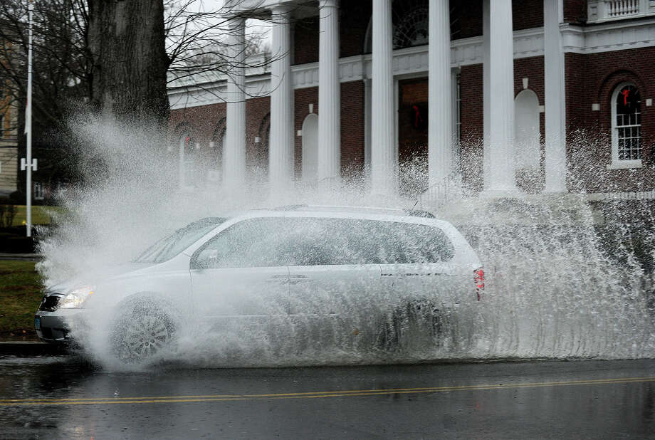 A minivan is obscured by spray as it is driven through a large rain puddle on River Street in front of City Hall in Milford, Conn. on Sunday, December 29, 2013. Photo: Brian A. Pounds / Connecticut Post