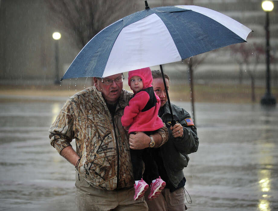 Robert, Tiffany, and Eva Hawley, 2, all of Newtown, share an umbrella to ward off a heavy rain as they walk from the parking area to the Sound Tigers hockey game at the Webster Bank Arena in Bridgeport, Conn. on Sunday, December 29, 2013. Photo: Brian A. Pounds / Connecticut Post
