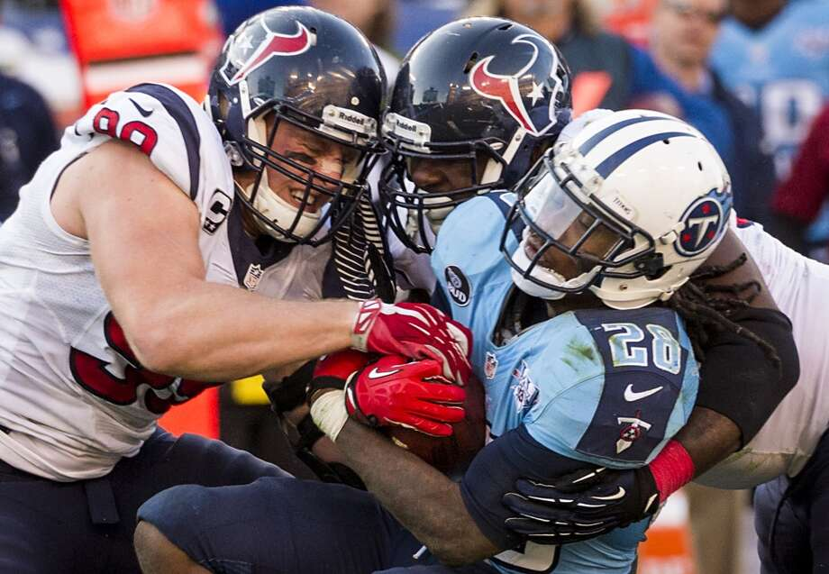 Texans defensive end J.J. Watt (99) and nose tackle Earl Mitchell bring down Titans running back Chris Johnson. Photo: Smiley N. Pool, Houston Chronicle