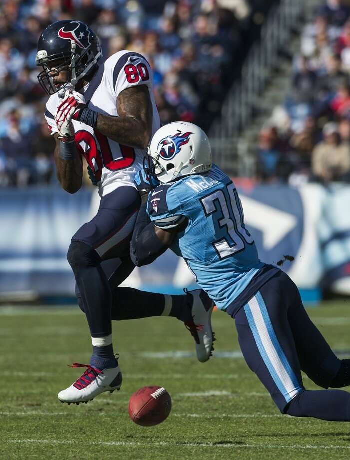 Texans wide receiver Andre Johnson has a pass go through his hands as Titans cornerback Jason McCourty defends. Photo: Smiley N. Pool, Houston Chronicle