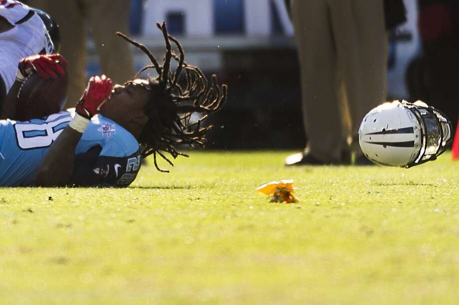 Titans running back Chris Johnson has his helmet knocked off after a run. Photo: Smiley N. Pool, Houston Chronicle