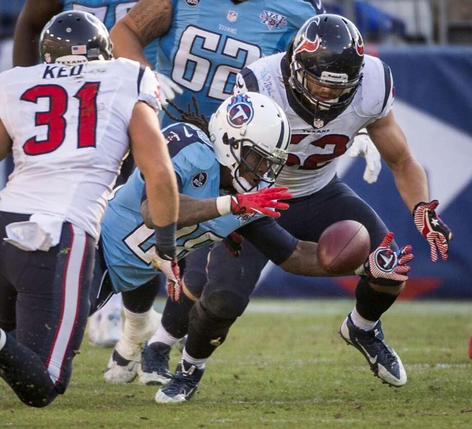 Titans running back Chris Johnson recovers his own fumble as Texans safety Shiloh Keo (31) and linebacker Jeff Tarpinian (52) look on. Photo: Smiley N. Pool, Houston Chronicle