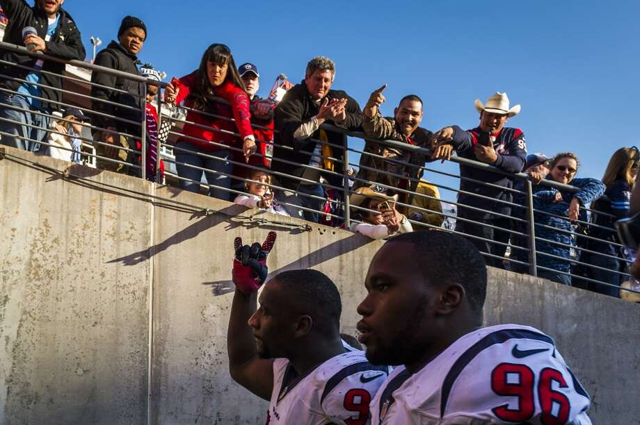 Texans defensive end Antonio Smith acknowledges fans as he leaves the field with  Tim Jamison. Photo: Smiley N. Pool, Houston Chronicle