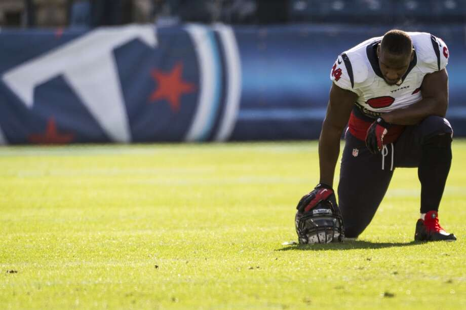 Antonio Smith of the Texans kneels on the field before playing the Titans. Photo: Smiley N. Pool, Houston Chronicle