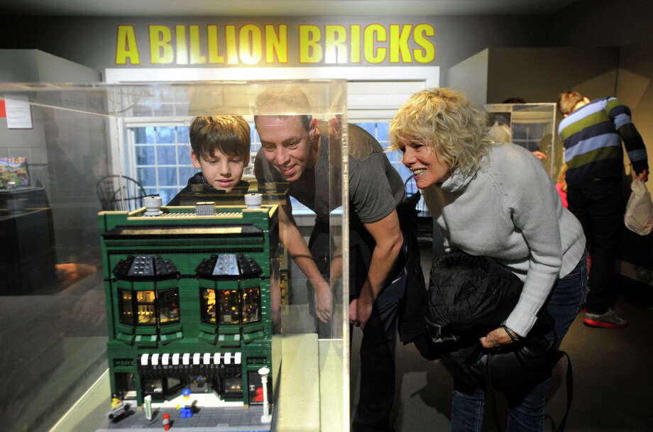 Gabe Shoffman, left, his father, Itai, and his grandmother, Monika Graves, look at a gallery piece on display during A Billion Bricks: LEGO T-Rex, Turtles & Trains exhibit at the Stamford Museum & Nature Center in Stamford, Conn., on Sunday, Dec. 29, 2013. This is the fifth season of the exhibit at the center. This year's exhibit is on display until March 2. Photo: Jason Rearick / Stamford Advocate