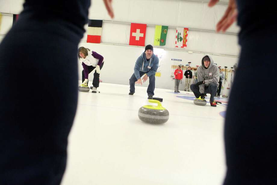 Louis Vitale, center, practices at the Learn to Curl class at the Nutmeg Curling Club in Bridgeport, Conn., on Sunday, Dec.29, 2013. The club offers introduction to curling classes, full lessons, and leagues for beginners. Photo: BK Angeletti, B.K. Angeletti / Connecticut Post freelance B.K. Angeletti