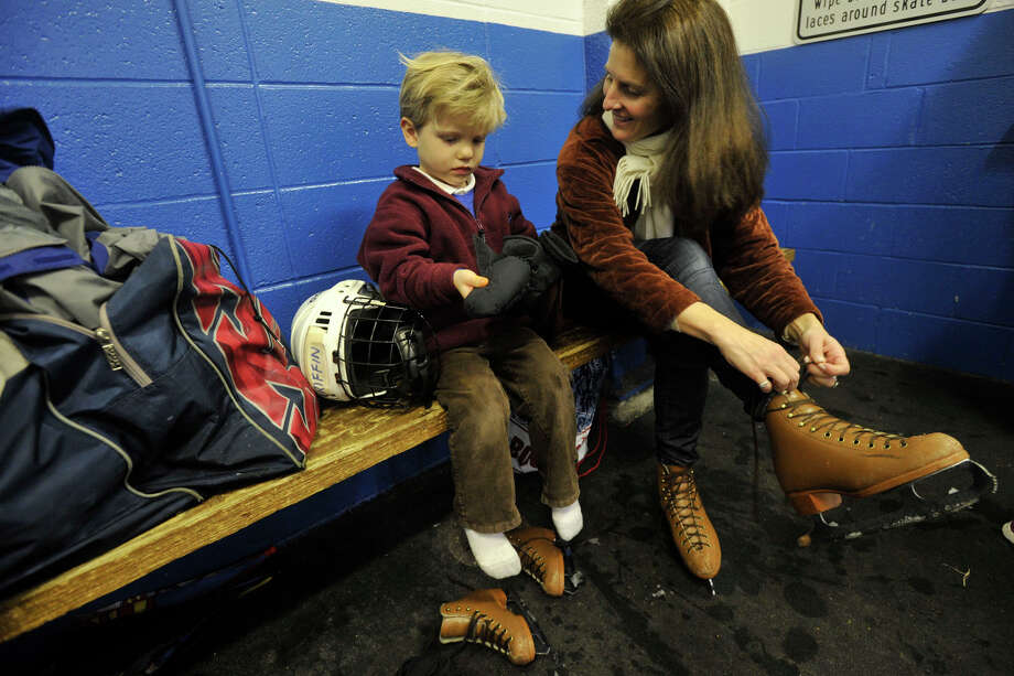 Victoria Cappiali and her son, Paul, remove their rental skates after the public skating session at Dorothy Hamill Skating Rink in Greenwich, Conn., on Sunday, Dec. 29, 2013. Photo: Jason Rearick / Stamford Advocate