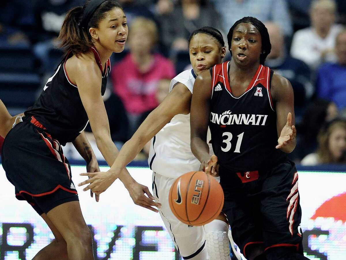 Connecticut's Moriah Jefferson, center, intercepts a pass-attempt from Cincinnati's Alyesha Lovett to Dayeesha Hollins, right, during the first half of an NCAA college basketball game on Sunday, Dec. 29, 2013, in Storrs, Conn.