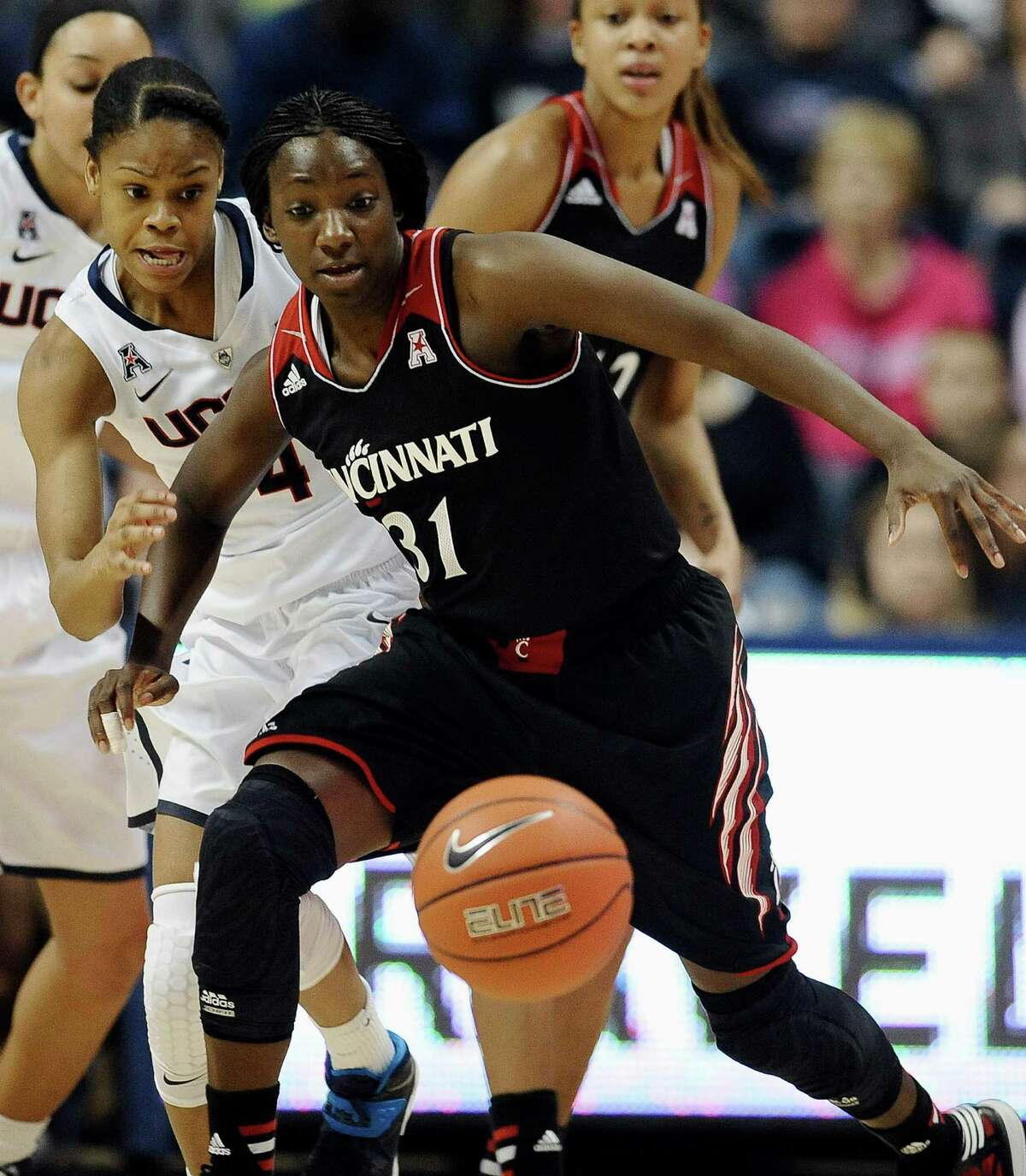 Connecticut's Moriah Jefferson, left, and Cincinnati's Dayeesha Hollins, right, chase a loose ball during the first half of an NCAA college basketball game on Sunday, Dec. 29, 2013, in Storrs, Conn.