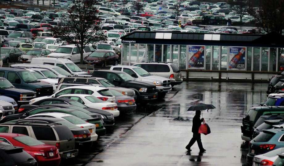 A shopper makes his way through the rain on his way into Crossgates Mall on Sunday, Dec. 29, 2013 in Albany, NY.   (Paul Buckowski / Times Union) Photo: PAUL BUCKOWSKI
