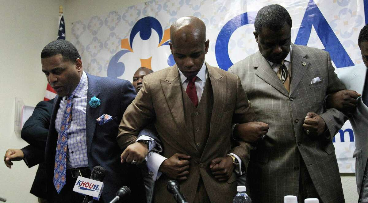 Activist Deric Muhammad, center, prays with Pastor E.A. Deckard, left, and Minister Robert Muhammad, after they spoke to the media Sunday about Conrad Barrett who allegedly punched a black man, 79, in a
