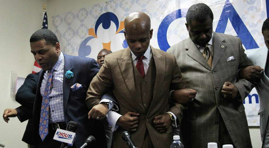 "Activist Deric Muhammad, center, prays with Pastor E.A. Deckard, left, and Minister Robert Muhammad, after they spoke to the media Sunday about Conrad Barrett who allegedly punched a black man, 79, in a ""knockout game"" attack. Photo: Karen Warren, Staff / © 2013 Houston Chronicle"