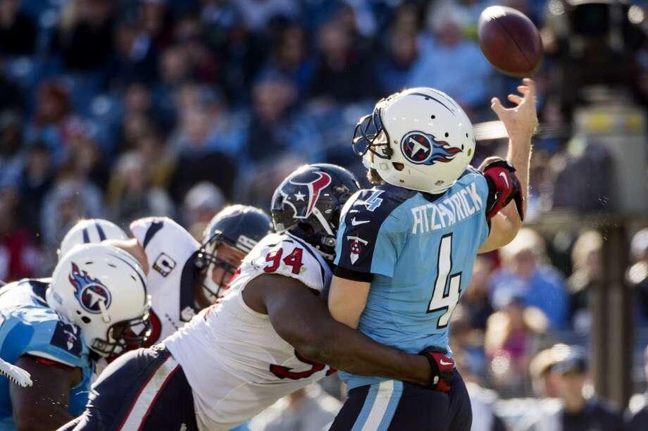 Titans quarterback Ryan Fitzpatrick (4) throws an interception as he is hit by Texans defensive end Antonio Smith (94). Photo: Smiley N. Pool, Houston Chronicle