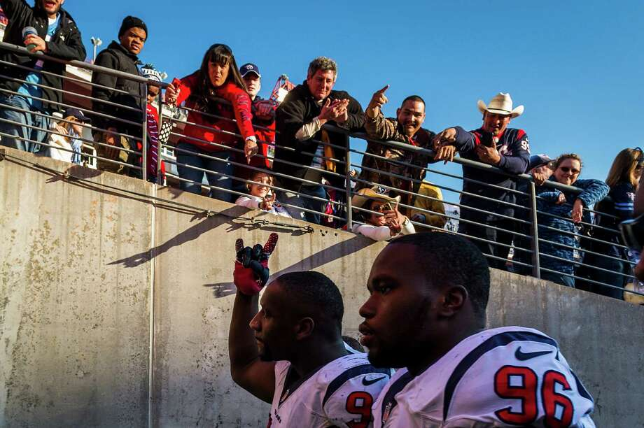 Despite the Texans ending the season with their 14th loss in a row, defensive ends Tim Jamison (96) and Antonio Smith got some encouragement from fans as they left the field Sunday in Nashville, Tenn. Photo: Smiley N. Pool, Staff / © 2013  Houston Chronicle