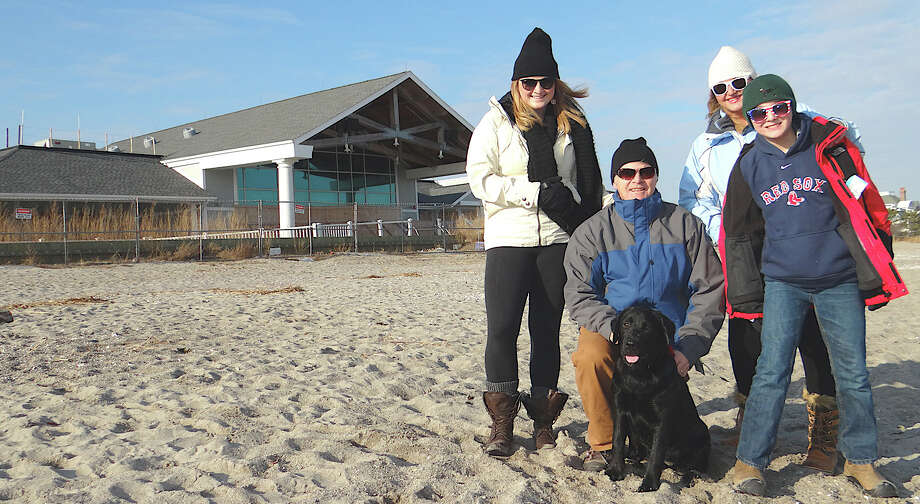 The Poler Family of Fairfield -- Reveley, Tim, Sara and Charlie -- with their black Labrador, Tessie, at Penfield Beach on Friday. Photo: Mike Lauterborn / Fairfield Citizen contributed