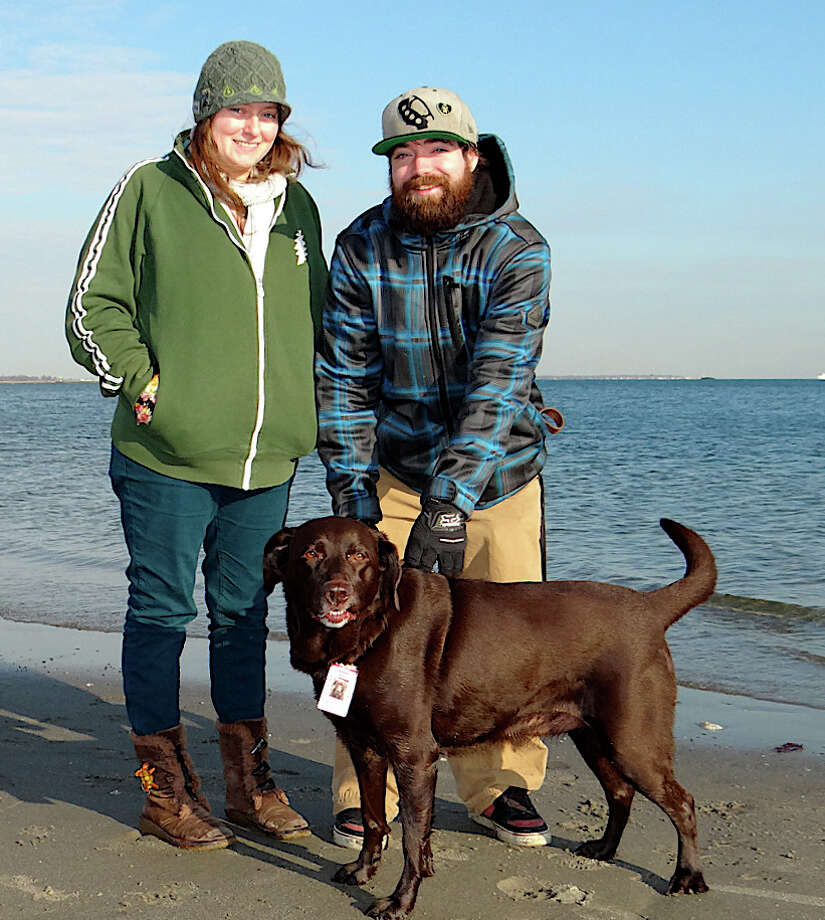 Brenna Dougherty of Simsbury and Will Quinn of Fairfield, with Bella, at Penfield Beach on Friday. Photo: Mike Lauterborn / Fairfield Citizen contributed