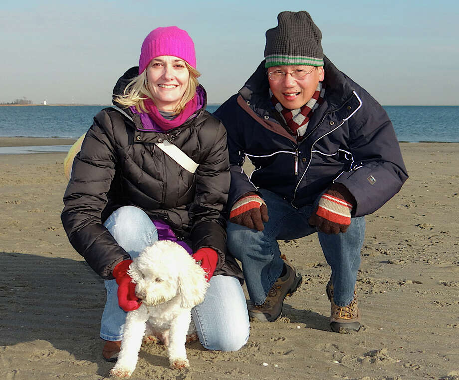 Greenwich residents Lissa Pasternak and Eric Tsang, with Casper, at Penfield Beach on Friday. Photo: Mike Lauterborn / Fairfield Citizen contributed