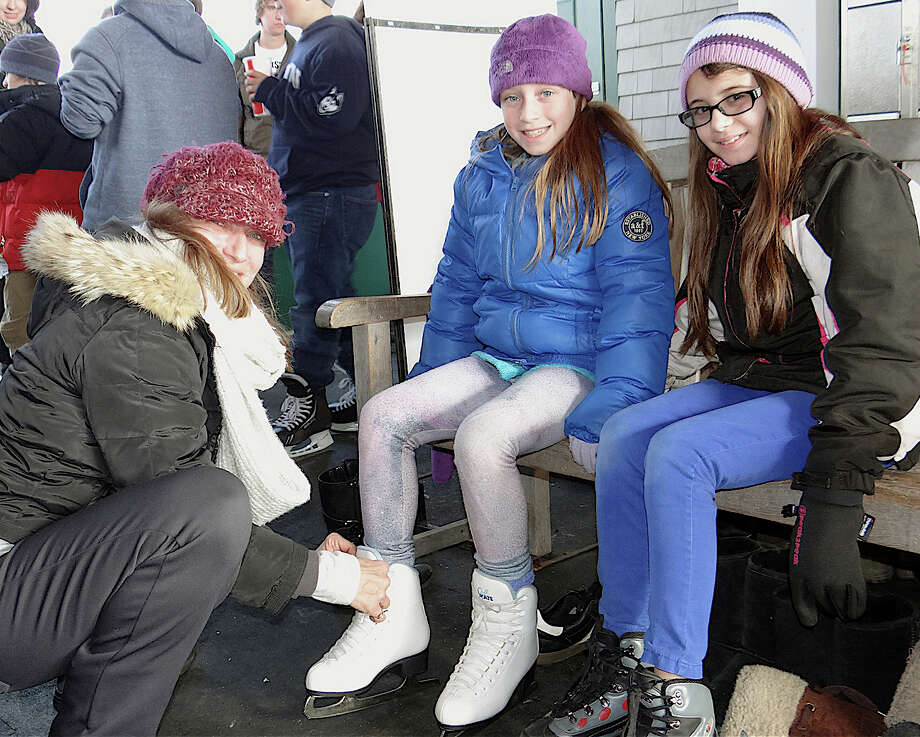 Kathy Buccellato, of Fairfield, laces up daughter Kayla's skates, while Kayla's friend Mallory Hart, 10, looks on Friday at the Westport PAL rink in Longshore Park. Photo: Mike Lauterborn / Westport News contributed
