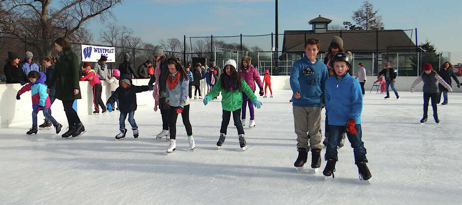Crowds glide through the holiday weekend Friday at the Westport Police Athletic League ice rink at Longshore Park. Photo: Mike Lauterborn / Westport News contributed