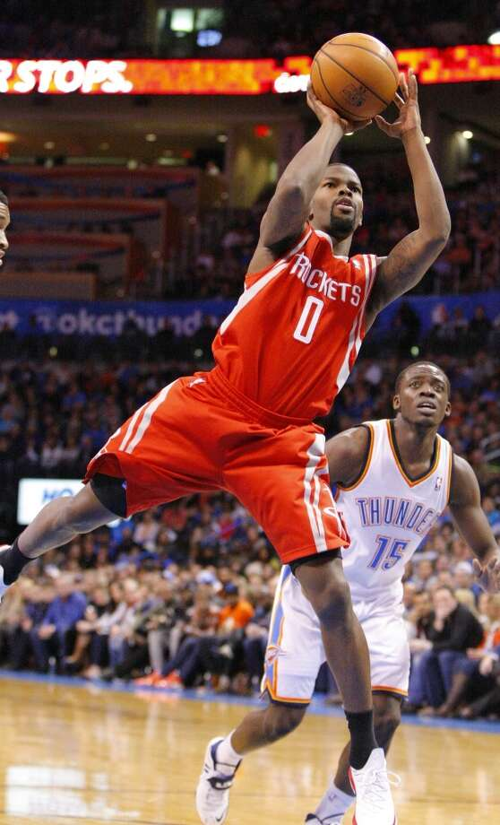 Rockets guard Aaron Brooks, left, shoots in front of Thunder guard Reggie Jackson. Photo: Alonzo Adams, Associated Press