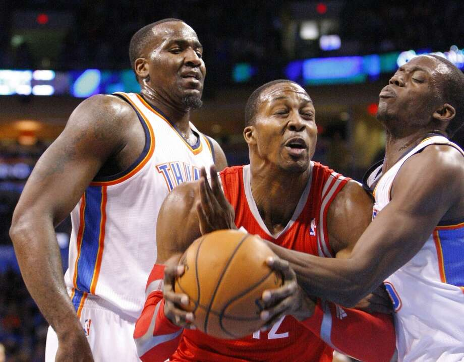 Rockets center Dwight Howard goes to the basket between the Thunder's Kendrick Perkins, left, and Reggie Jackson. Photo: Alonzo Adams, Associated Press