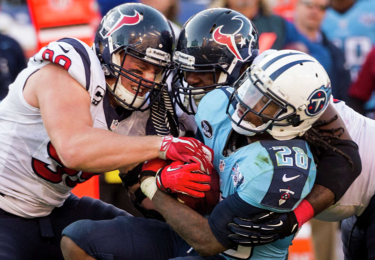 Texans defensive end J.J. Watt (99) and nose tackle Earl Mitchell, center, get grabby with Titans running back Chris Johnson (28) in the second half.