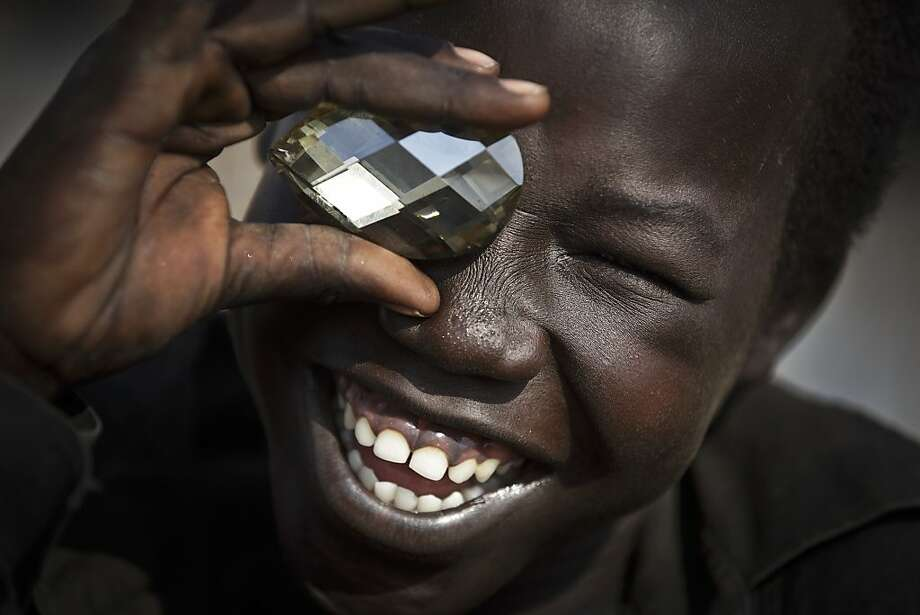 Carats are good for the eyes: A boy with a plastic jewel mimics a photographer taking a picture of him at a United Nations compound that has 